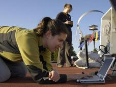 Two students work with photovoltaic panel testing equipment on a roof