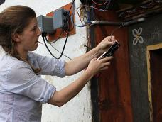 A graduate student installs a mini-grid device on a house in Bhutan
