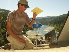 A student works with a Solar Pathfinder device on a Yurok reservation with a river visible in the background
