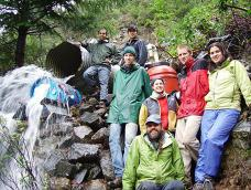 A group of students pose near the water pouring out of a culvert pipe
