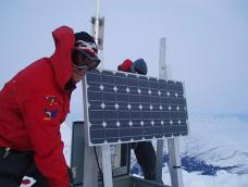 Two people in mountain gear install a solar-powered repeater on a snow-covered mountain top